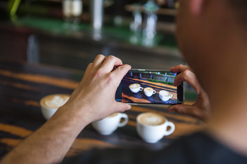 Man taking cell phone picture of cappuccino cups