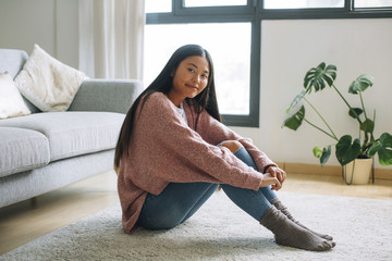 Portrait of smiling young woman with sitting on the floor at home