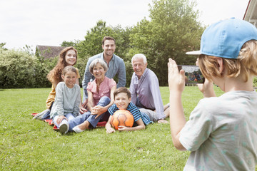 Boy taking picture of happy extended family in garden