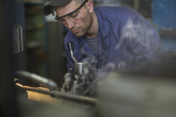 Mechanic wearing safety goggles using machine in workshop