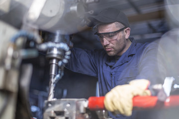 Mechanic wearing safety goggles using drilling machine in workshop