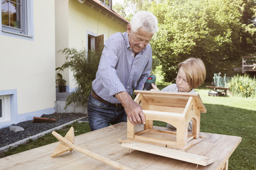 Grandfather and grandson building up a birdhouse