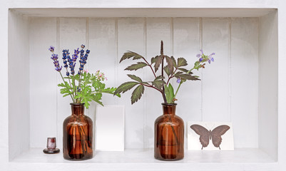 Shelf with lavender and geranium in old pharmacy bottles.