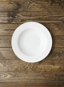An empty white dinner plate on a rustic wooden background