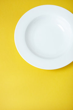 An empty white dinner plate on a yellow background