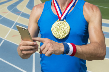 American gold medal athlete standing at running track using his mobile phone