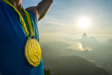 Gold medal champion athlete standing outdoors at the golden sunrise at Rio de Janeiro skyline
