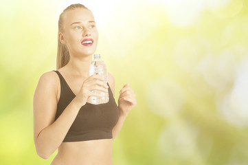 Pretty female runner resting and drinking water from a bottle  on a green background