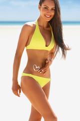 Happy woman in bikini posing on beach, sun cream in shape of heart