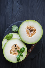 Above view of sliced juicy melon on a black wooden background