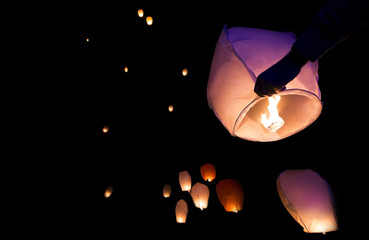 Chinese lanterns take flight in the dark night sky, make a wish