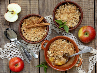 Cheese casserole or crumble with apples and cinnamon in brown cup ramekin on wooden background