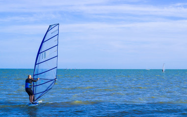 Lone windsurfer back-first in the sea catching a wave