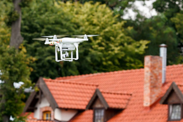 Modern RC Quadcopter. RC Drone with camera flying over the roof of the house. selective focus