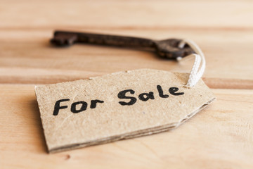 The concept of sale of property - old key, inscribed on label on wooden background.