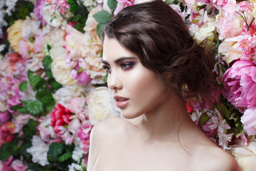 Profile of beautiful fashion girl, sweet, sensual. Beautiful makeup and messy romantic hairstyle. Flowers background.
