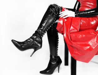 Donna seduta con stivali e abiti in pelle e latex