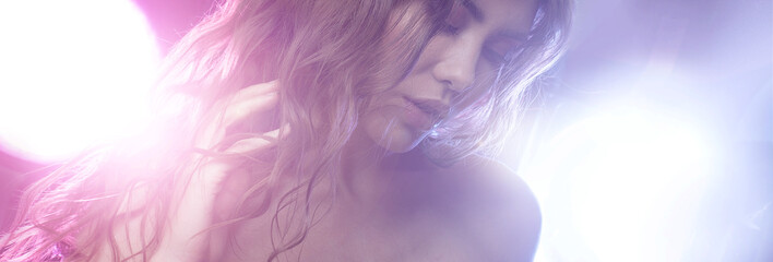 Young beautiful girl brunette, amid spotlight. Night club, dance culture. Effect of illumination