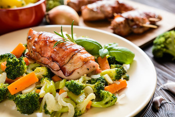 Baked chicken breast wrapped in bacon slices with boiled potatoes and steamed broccoli, carrot, garlic, onion