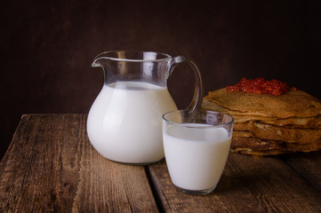 Glass jug and glass with milk on a wooden rustic background.