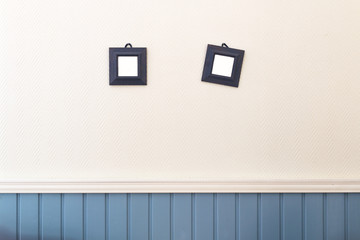 Two small square frames hanging on the white and blue wall.
