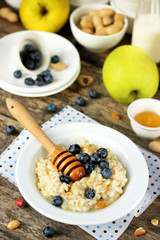 Oatmeal with blueberries, peanuts, honey on the wooden table