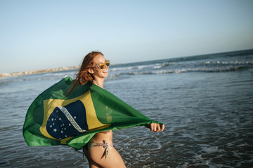 Red-haired girl wearing Brazilian flag in water on beach