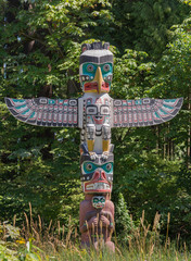 Vancouver, Canada - July 24, 2016: One of nine totem poles at Hallelujah point in Stanley Park. Detailed colors and features. Small wings. Dark colors fight with white hue. Green trees as background.