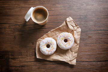 Paper cup of coffee and doughnuts on wooden background