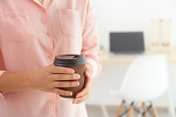 Female hands holding paper cup of coffee indoors