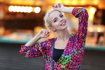 Fashionable young woman posing on city lights background