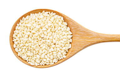 white sesame seeds in wooden spoon.
