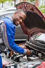 Mechanic Testing Car Battery With Multimeter
