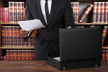 Lawyer Removing Papers From Briefcase