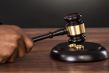 Judge Hands Hitting Gavel At Desk