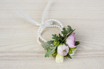 Wrist corsage made of ranunculus and freesia flowers.