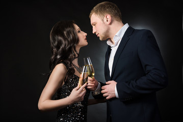 couple full dressed drinking champagne on black background