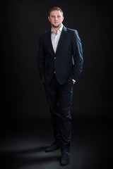 Portrait of handsome stylish man in elegant suit on black background