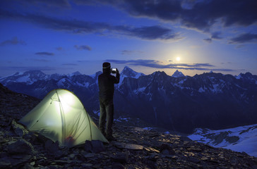 Mountaineer taking a photo with his smartphone of the moon rising above the famous Matterhorn mountain, Switserland.