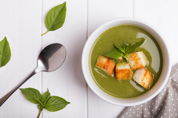 Green healthy cream soup on white background