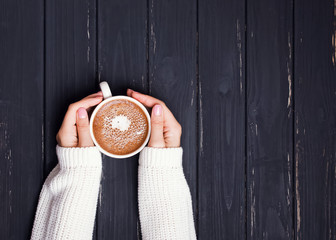 Fotobehang - Woman's hands in sweater holding cup of coffee