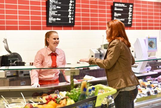 Frau im Supermarkt an einer Theke mit einer freundlichen Verkäuferin // Woman in a supermarket at a bar with a friendly saleswoman