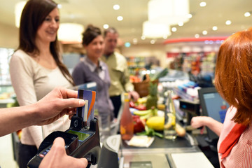 Kartenzahlung im Supermarkt an der Kasse // Credit card payments at the grocery store at checkout