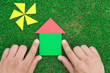 House and sun made of tangram figures on natural grass. Man's ha