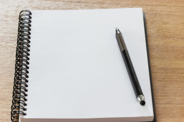 Blank notebook on the wooden desk background with a pen on top.