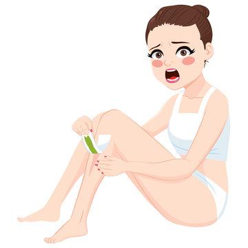 Beautiful brunette woman doing leg waxing epilation showing hurting and painful facial expression