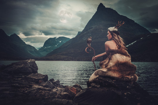 Nordic goddess in ritual garment with hawk near wild mountain lake in Innerdalen valley.
