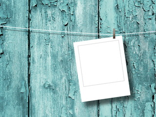 Close-up of one blank square instant photo frame hanged by peg against aqua scratched wooden boards background