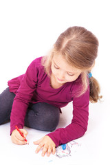 Little cute girl draws pencils sitting on the floor