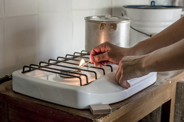woman lights the match the gas stove on which stands a pan by in a village house